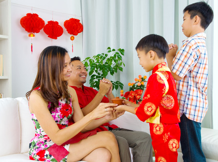 celebrate year: Asian boy presenting tea to his mother during chinese new year
