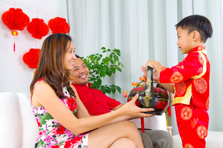 gift basket: Asian boys presenting gift basket to parents on chinese new year