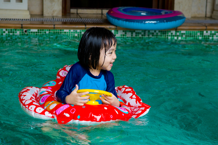 health concern: asian child in swim tube playing on swimming pool