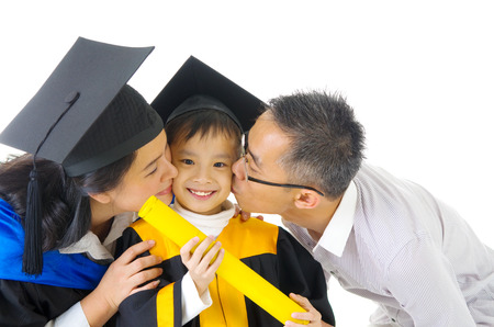mortarboard: Asian kindergarten child in graduation gown and mortarboard kissed by her parent during graduation