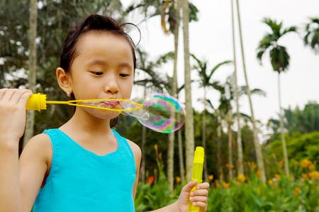 niñas chinas: burbujas de Asia soplan de la chica al aire libre Foto de archivo