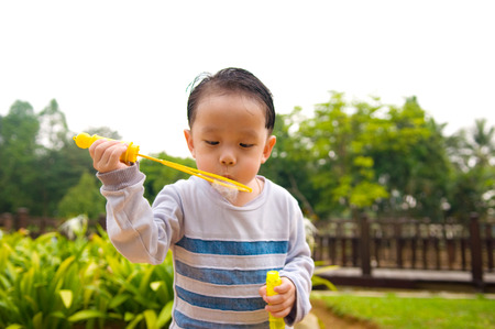 blowing bubbles: Asian boy blowing bubbles outdoor Stock Photo