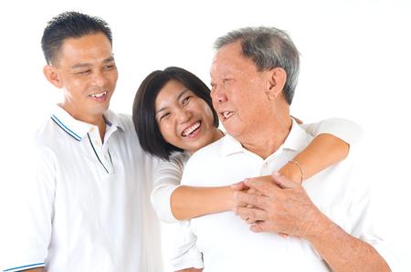 embrace family: Hombre mayor con su hijo e hija. Familia asiática feliz al padre mayor y adultos vástagos tengan tiempo de diversión en el estudio de interiores. Foto de archivo