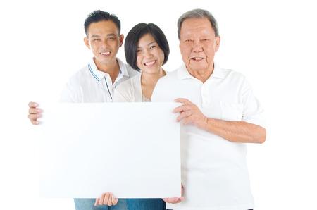 hijos: Hombre mayor con su hijo e hija. Familia asiática feliz al padre mayor y adultos descendientes sosteniendo un cartel en blanco sobre fondo aislado. Foto de archivo