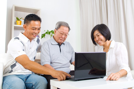 learns: Asian senior man learns to use tablet computer Stock Photo
