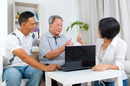 senior adult woman: Asian senior man learns to use tablet computer Stock Photo