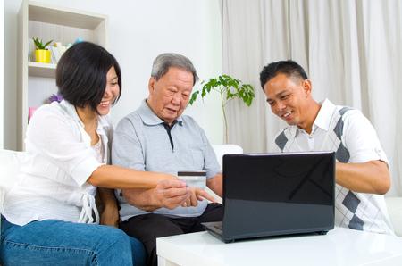 hombre viejo: Hombre mayor asiático aprende a utilizar la banca en línea de internet Foto de archivo