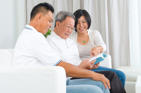 old asian: Asian family reading book at home