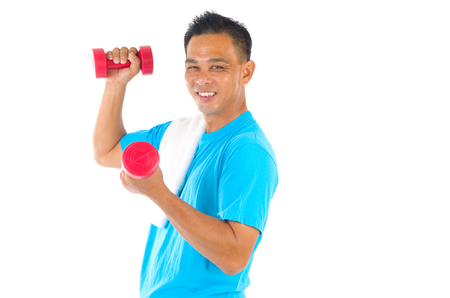 free weights: Portrait of fitness man working out with free weights in studio Stock Photo