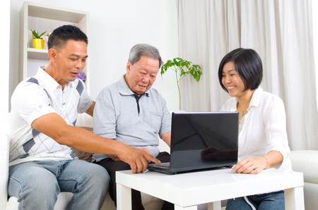 Asian senior man learns to use tablet computer Stock Photo