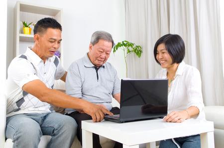 damas antiguas: Hombre mayor asi�tico aprende a usar la computadora de la tableta
