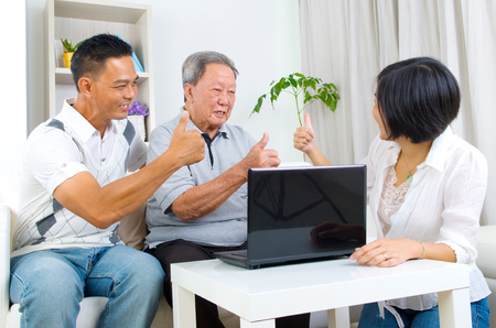 80s adult: Asian senior man learns to use tablet computer Stock Photo