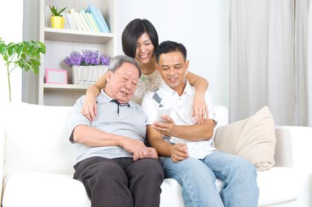 adult 80s: Modern technology, age and people concept. Asian senior man with his daughter and son taking selfie, using smartphone, self photographing.