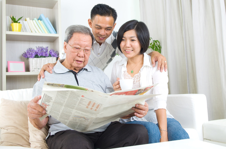 Portrait of chinese family reading newspaper together at home. Mature 80s senior man and his children.
