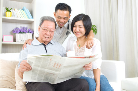 senior reading: Portrait of chinese family reading newspaper together at home. Mature 80s senior man and his children.