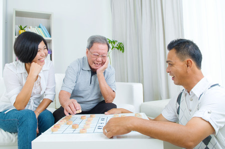 old asian: Chinese family playing Chinese chess at home, senior father with his  adult son and daughter.