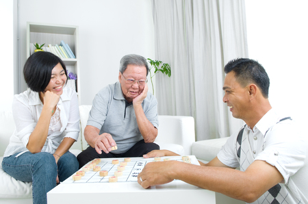 chinese adult: Chinese family playing Chinese chess at home, senior father with his  adult son and daughter.