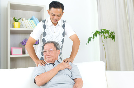 Asian old man shoulder pain, sitting on sofa , son massaging father shoulder. Chinese family, senior retiree indoors living lifestyle at home.