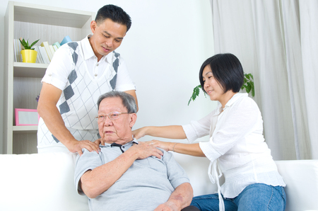 retiree: Asian old man shoulder pain, sitting on sofa , daughter and son massaging their father shoulder. Chinese family, senior retiree indoors living lifestyle at home.