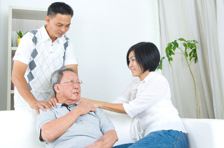 Asian old man shoulder pain, sitting on sofa , daughter and son massaging their father shoulder. Chinese family, senior retiree indoors living lifestyle at home.