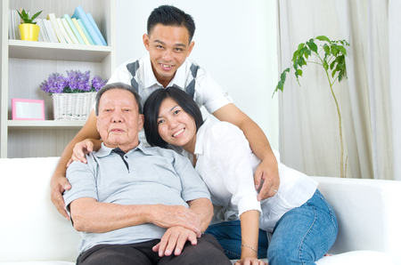 family looking up: Asian senior father with his adult son and daughter at home. Family living lifestyle. Stock Photo