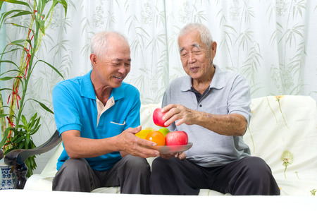 70s adult: Happy asian family eating healthy fruit. Stock Photo