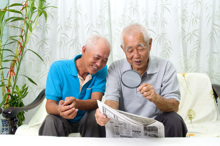 old asian: Portrait of chinese family reading newspaper together at home. Mature 80s senior man and his son