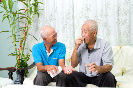 caring for: Asian senior man having medicine at home. Adult son caring for a senior man. Stock Photo