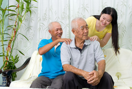 problemas familiares: Asian old man shoulder pain, sitting on sofa , grandchild and son massaging their father and grandfather shoulder. Chinese family, senior retiree indoors living lifestyle at home.