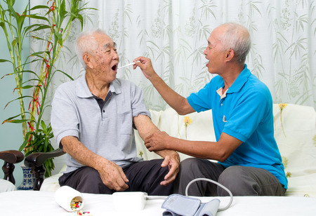 body temperature: Asian man is checking his fathers body temperature with a digital thermometer. Stock Photo