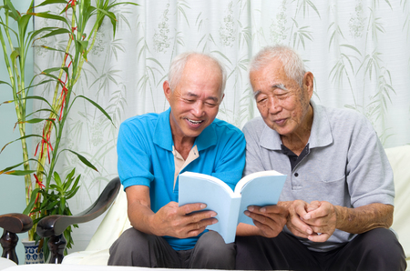 old asian: asian senior man reading a book with his son at home