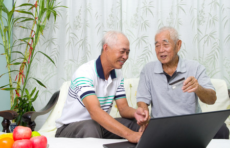 learns: Asian senior man learns to use online internet banking Stock Photo