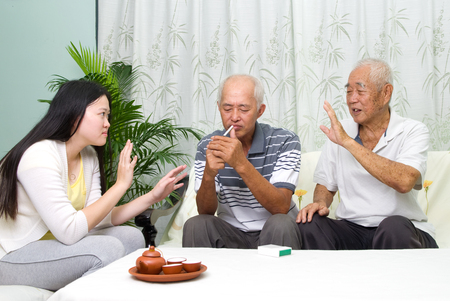 problemas familiares: Asian father smoking at home. Unhealthy lifestyle or stop smoking concept photo.