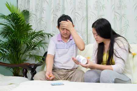 personne malade: Asian man having medicine at home. Daughter take care of her father.