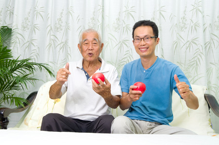 old asian: Asian senior man and son making okay sign while holding an apple