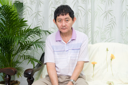 needy: Mentally disabled man sitting on the sofa at home looking at camera. Stock Photo