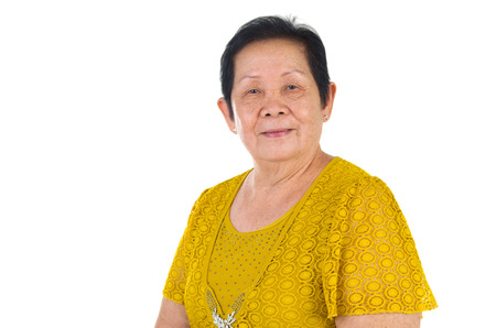 koreans: happy asian senior female smilling in the studio. senior adult asian chinese woman standing isolated white background Stock Photo