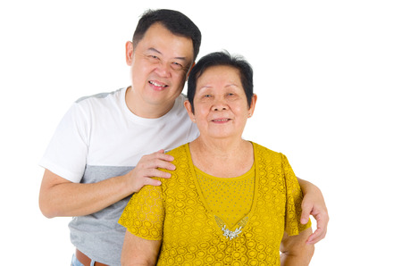 adult offspring: Senior woman and son. Happy Asian family senior mother and adult offspring having fun time at indoor studio. Stock Photo