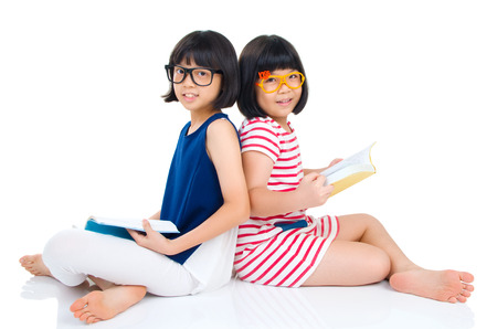 wearing spectacles: Asian girls wearing spectacles sitting on the floor with books