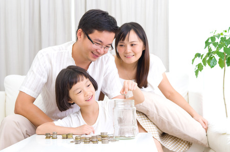 Asian kid putting coins into the glass bottle Stock Photo