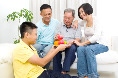 80s adult: Happy asian family eating healthy fruit. Stock Photo