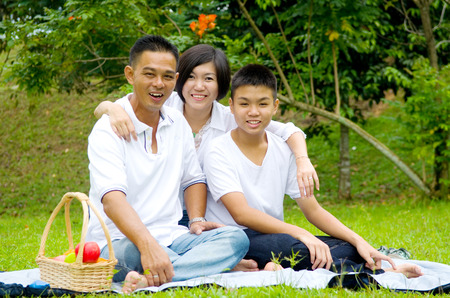 family with three children: Asian Chinese Family Relaxing at outdoor park Stock Photo