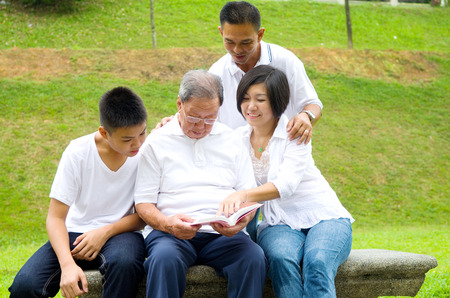 Asian three generation family reading book at outdoor park