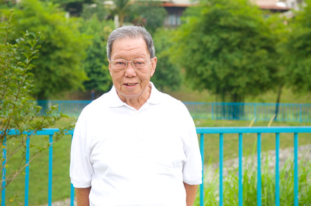 80s adult: Portrait of a smiling asian senior man at outdoor park
