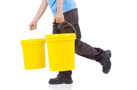 lubricant: Production worker carrying two buckets of lubricant oils and greases, isolated on white background. Stock Photo