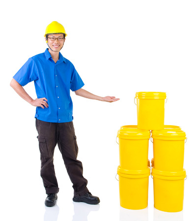 distributor: Lubricant oils and greases distributor with suit hardhat pointing his hand over the products, thumb-up, isolated on white background.