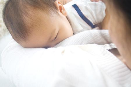 Asian mother breastfeeding her baby boy Stock Photo