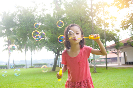 girl blowing: Asian girl blowing bubbles outdoor