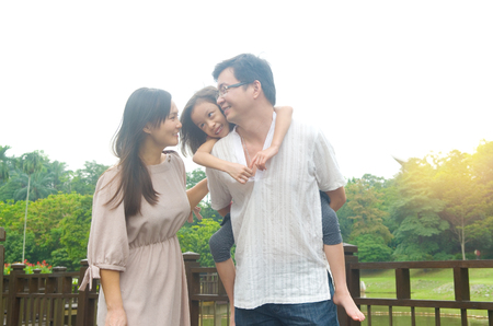 Happy Asian family outdoor. Father piggybacking his daughter walking in garden park with wife. Healthy lifestyle. Stock Photo