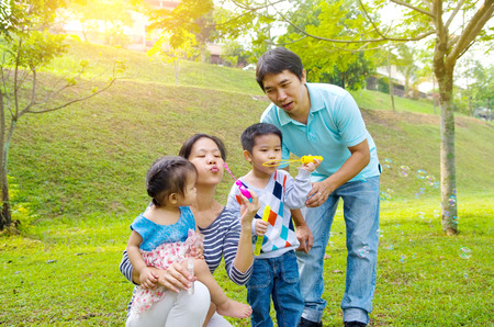 blowing bubbles: Asian family blowing bubbles outdoor
